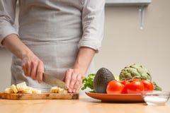 E Ένας αρχιμάγειρας κόβει το τυρί μοτσαρελών ή φέτα, ανακατώνει, κατά τη διάρκεια μιας χορτοφάγου σαλάτας στην εγχώρια κουζίνα r στοκ φωτογραφίες με δικαίωμα ελεύθερης χρήσης