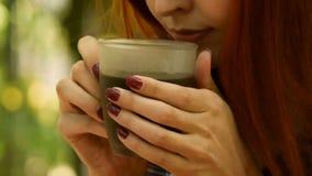 E Ένα θηλυκό χέρι παίρνει ένα φλιτζάνι του καφέ και το φέρνει στα χείλια της Η φύση φιλμ μικρού μήκους