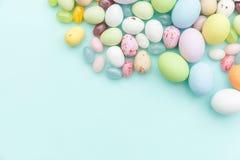 E Αυγά σοκολάτας καραμελών Πάσχας και jellybean γλυκά που απομονώνονται στο καθιερώνον τη μόδα μπλε υπόβαθρο κρητιδογραφιών r στοκ φωτογραφίες με δικαίωμα ελεύθερης χρήσης