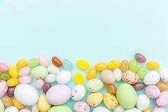 E Αυγά σοκολάτας καραμελών Πάσχας και jellybean γλυκά που απομονώνονται στο καθιερώνον τη μόδα μπλε υπόβαθρο κρητιδογραφιών r στοκ φωτογραφία