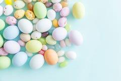 E Αυγά σοκολάτας καραμελών Πάσχας και jellybean γλυκά που απομονώνονται στο καθιερώνον τη μόδα μπλε υπόβαθρο κρητιδογραφιών r στοκ εικόνα