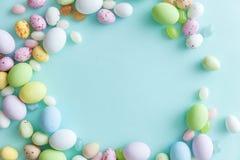 E Αυγά σοκολάτας καραμελών Πάσχας και jellybean γλυκά που απομονώνονται στο καθιερώνον τη μόδα μπλε υπόβαθρο κρητιδογραφιών r στοκ εικόνες