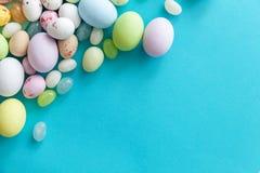 E Αυγά σοκολάτας καραμελών Πάσχας και jellybean γλυκά που απομονώνονται στο καθιερώνον τη μόδα μπλε υπόβαθρο κρητιδογραφιών r στοκ εικόνα με δικαίωμα ελεύθερης χρήσης