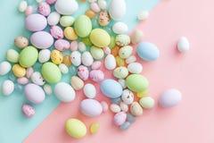 E Αυγά σοκολάτας καραμελών Πάσχας και jellybean γλυκά που απομονώνονται στο καθιερώνον τη μόδα μπλε ρόδινο υπόβαθρο κρητιδογραφιώ στοκ φωτογραφία με δικαίωμα ελεύθερης χρήσης