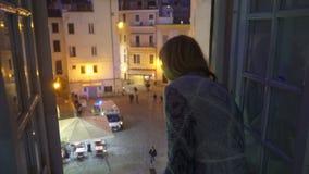 E Αυτοκίνητο ασθενοφόρων στην οδό Η συγκινημένη νέα γυναίκα φαίνεται έξω το παράθυρο του σπιτιού της απόθεμα βίντεο