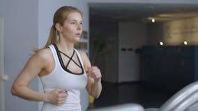 E Γυναίκα που τρέχει treadmill απόθεμα βίντεο