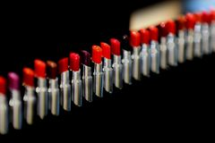 E Διαφορετικές σκιές του κόκκινου χρώματος Σύνολο κραγιόν, συλλογή στο μαύρο υπόβαθρο Visage και makeup για στοκ εικόνες