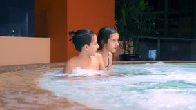 E δύο έφηβοι παιδιών που χαλαρώνουν στο ζεστό νερό κοντά στη λίμνη απόθεμα βίντεο