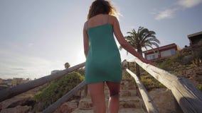E Η νέα γυναίκα πηγαίνει από την παραλία αναρριμένος επάνω στα σκαλοπάτια Ένας περίπατος γυναικών επάνω τα σκαλοπάτια το απόγευμα απόθεμα βίντεο