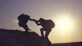 E Η ομάδα τουριστών δανείζει ένα χέρι βοηθείας αναρριχείται στον τρόπο ζωής οι απότομοι βράχοι φιλμ μικρού μήκους