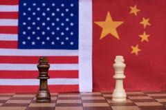 E Η στάση δύο βασιλιάδων αντιμετωπίζει με το υπόβαθρο εθνικών σημαιών των ΗΠΑ και της Κίνας E r στοκ εικόνες