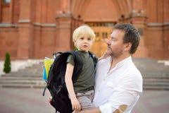 E Λίγος μαθητής με τον πατέρα του Πρώτη ημέρα του δημοτικού σχολείου στοκ φωτογραφία