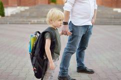 E Λίγος μαθητής με τον πατέρα του Πρώτη ημέρα του δημοτικού σχολείου στοκ εικόνες