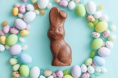 E Λαγουδάκι αυγών σοκολάτας καραμελών Πάσχας και jellybean γλυκά που απομονώνονται στο καθιερώνον τη μόδα μπλε υπόβαθρο κρητιδογρ στοκ φωτογραφία