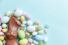 E Λαγουδάκι αυγών σοκολάτας καραμελών Πάσχας και jellybean γλυκά που απομονώνονται στο καθιερώνον τη μόδα μπλε υπόβαθρο κρητιδογρ στοκ φωτογραφίες