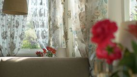 E Μια χαριτωμένη ανθοδέσμη των κόκκινων τριαντάφυλλων και του freesia σε ένα βάζο σε έναν πίνακα μια ηλιόλουστη θερινή ημέρα σε έ στοκ εικόνες