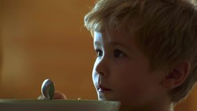 E Μικρό παιδί που έχει το πρόγευμα στην κουζίνα Το ευτυχές κουτάλι αγοράκι τρώεται Μωρό που τρώει τα τρόφιμα στην κουζίνα φιλμ μικρού μήκους