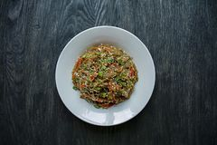 E Σαλάτα των νουντλς σελοφάν, που τηγανίζεται με τα λαχανικά, που διακοσμούνται με τα πράσινα και τα ραβδιά καβουριών Funchoza Κα στοκ φωτογραφίες με δικαίωμα ελεύθερης χρήσης