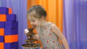 E Τα παιδιά τρώνε τη σοκολάτα από μια πηγή σοκολάτας απόθεμα βίντεο