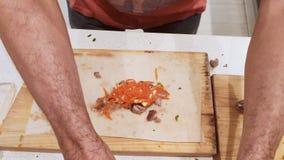 E τα χέρια των ατόμων προετοιμάζουν το shawarma Η διαδικασία του εύγευστου shawarma μαγειρέματος με το κρέας, λαχανικά και ξινός φιλμ μικρού μήκους