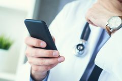 E Χέρια γιατρών με το κινητό τηλέφωνο στοκ φωτογραφία με δικαίωμα ελεύθερης χρήσης