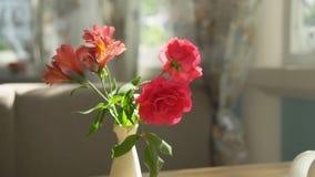 E Χαριτωμένη ανθοδέσμη των κόκκινων τριαντάφυλλων και του freesia σε ένα βάζο σε έναν πίνακα μια ηλιόλουστη θερινή ημέρα σε έναν  απόθεμα βίντεο