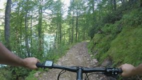 E-велосипед катания человека POV вдоль озера Путь следа велосипедиста действия Mtb исследуя около древесин леса горы bike электри акции видеоматериалы