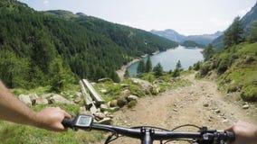 E-велосипед катания человека POV на покатом близко озере Путь следа велосипедиста действия Mtb исследуя около гор bike электричес видеоматериал