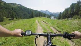 E-велосипед катания человека POV на покатом близко озере Путь следа велосипедиста действия Mtb исследуя около гор bike электричес сток-видео