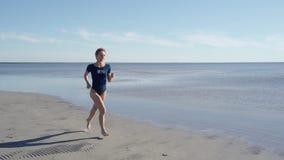E Девушка jogging вдоль берега океана r o сток-видео