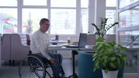 E-дело, успешный зрелый мужчина инвалидный в стеклах кресло-коляскы нося использует ноутбук сидя на таблице в кафе видеоматериал
