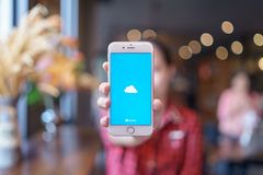 E 08,2019: Женщина держа iPhone 6S Яблока подняла золото с OneDrive на экране Майкрософт OneDrive файл стоковая фотография