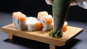 E Концепция еды замедленного движения Конец-вверх профессионального шеф-повара Лить wasabi на деревянной плите с кренами суш сток-видео