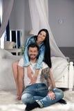 E Красивые молодые пары скрепляя и усмехаясь пока сидящ в спальне стоковое изображение rf