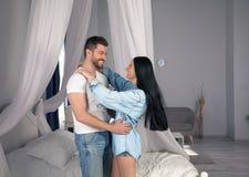 E Красивые молодые пары скрепляя и усмехаясь пока сидящ в спальне стоковые изображения