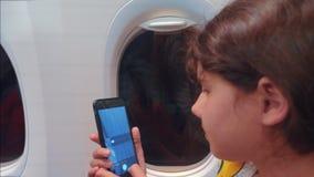 E маленькая девочка летает на самолет внутри фотографирует на городе ночи смартфона ниже видеоматериал