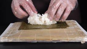 E Мастер суш распространяет рис на nori ( Шеф-повар суш подготавливая рис для крена суш изолированного на черноте видеоматериал
