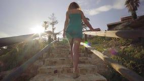 E Молодая женщина идет от пляжа взбираясь вверх лестницы Прогулка женщины вверх по лестницам после обеда сток-видео