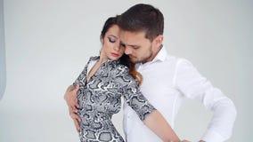 E Молодые красивые пары танцуя чувственный танец на белой предпосылке сток-видео