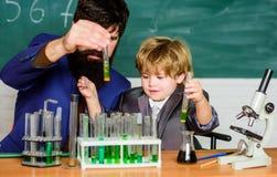 E Объяснять биологию ребенку отец и сын в школе biotechnoloy концепция исследования Химия и стоковое фото rf
