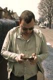 E 18-ое апреля 2019 Портрет реального, обычный человек идя проверяющ умный телефон в улице r стоковое фото