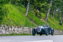 E 15-ое мая 2019: Исторические автогонки Mille Miglia Пара спеша в красивом зеленом годе сбора винограда стоковые фотографии rf