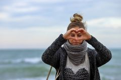 E Отправьте вами мое сердце Красивая девушка показывает рукам знак сердца Молодое белокурое усаживание на камнях с морем дальше стоковые фотографии rf