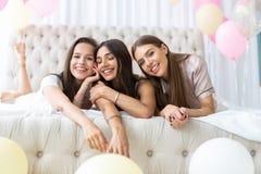E Привлекательные молодые усмехаясь женщины в пижамах выпивая шампанское пока имеющ девичник в спальне стоковое фото