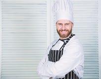E Профессионал в кухне r уверенный человек в рисберме и шляпе повар в ресторане, форме стоковое изображение