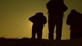 E 3 путешественника спускают от холма в лучах солнца одного после того как другой идет за горизонтом o сток-видео