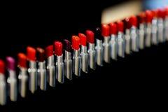 E Различные тени красного цвета Установите губной помады, собрания на черной предпосылке Выражение лица и макияж для стоковое фото