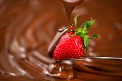 E Расплавленный шоколад лить на свежем зрелом сочном крупном плане клубники над предпосылкой коричневого цвета свирли fondue стоковое фото