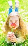 E Ребенок наслаждается днем весны солнечным пока лежащ на луге с цветками Девушка дальше стоковое изображение
