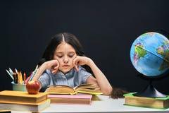 E сконцентрированный красивый студент читая книгу сидя на таблице Ребенок в классе с доской в стоковые фото